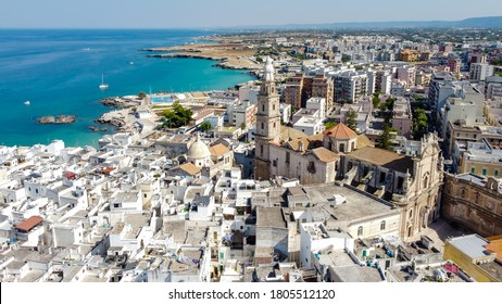 Aerial view of Monopoli in Apulia, south of Italy - Monopoli Cathedral aka Basilica of the Madonna della Madia from above, in front of the Adriatic Sea