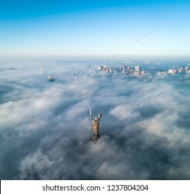 Aerial view of the Monument Motherland, shrouded in thick fog at dawn, Kiev, Ukraine. The concept of the apocalyptic doomsday. City in the mist