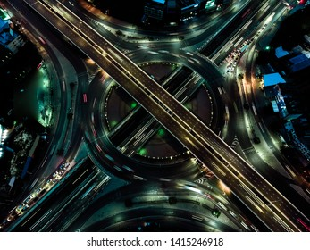 Aerial view of Morden city and smart transportation with Expressway, Road and Roundabout, busy highway traffic night time. Important infrastructure.