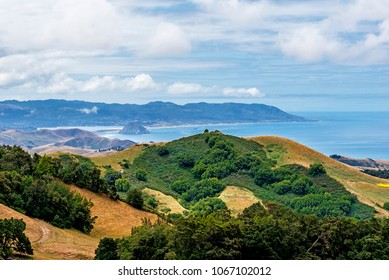 Aerial view of Morro Rock, Morro Bay, Montana de Oro & rural coastal hills / mountains, blue sky, white clouds, as seen from Highway 46 on the Big Sur coast, California Central Coast, near Cambria CA