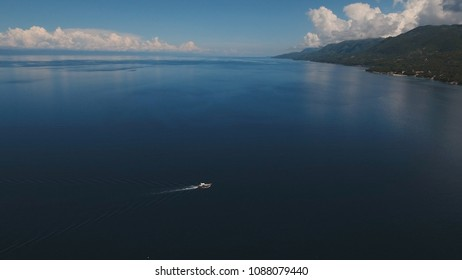 Aerial view of motor boat in sea. Aerial image of motorboat floating in a turquoise blue sea water. Sea landscape with wake of small fast motorboat. Tropical landscape. Philippines, Cebu. Travel
