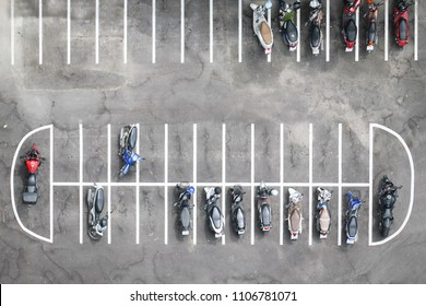 Aerial view of motorcycles parking row on concrete floor.
