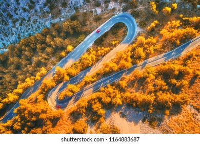 Aerial view of mountain curve road with cars, orange forest at sunset in autumn in Europe. Landscape with asphalt road, trees on the rocks. Highway through the park. Top view from flying drone. Fall