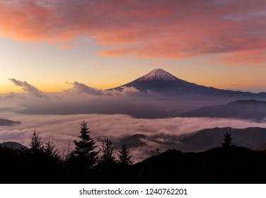 Aerial view of Mountain Fuji with morning mist or fog at sunrise in Fujikawaguchiko, Yamanashi, Japan. Landscape with hills.
