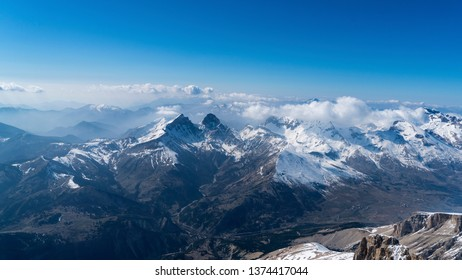 Aerial view of mountain ridge in the French Alps. Peaks of 3000 meter high with snow, clouds and a crystal clear blue sky and horizon.