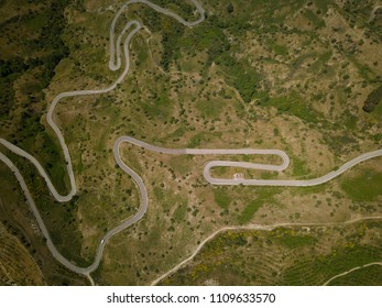 Aerial view of a mountain route with curves near to Etna volcano, Sicily, Italy. Ruined building and car.