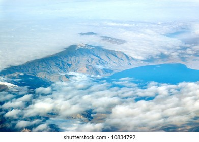 Aerial view of mountains and lake shrouded by clouds and mist.  Blue lake.