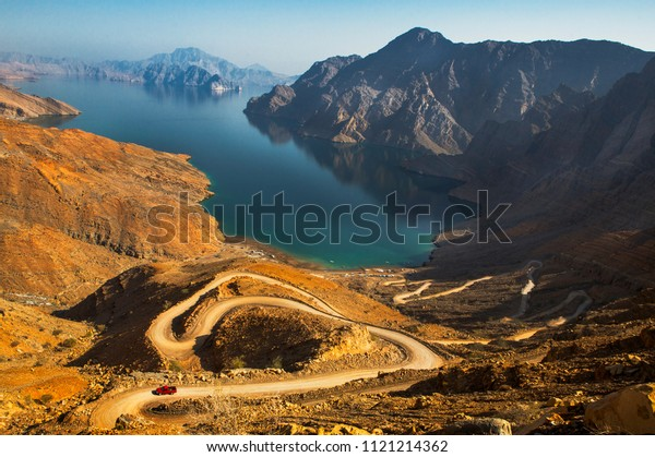 An aerial view of the mountains in Oman that show an adventurous curve of the road leading to the main tourist place in Musandam, Kassab.