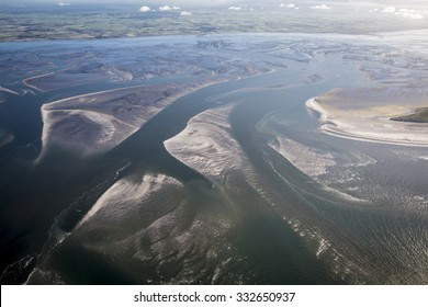 aerial view of the mudflat coastline at low tide with water winding in the mud and sand bank, Frisian island Ameland, The Netherlands
