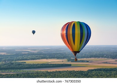 Aerial view of multicolored hot air balloons flying over a forest on evening lighting