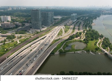 Aerial view of multiple lane highway and traffic beside lake.