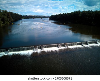 Aerial view of murky brown water gushing over the Nepean River Weir on a sunny summer day, sun reflecting off water, sparkling, river weeds, lush green trees. Penrith NSW, Australia - Shutterstock ID 1905508591