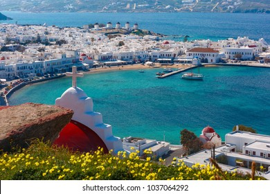 Aerial view of Mykonos City, Chora with Old Port, white houses, windmilles and churches on the island Mykonos, The island of the winds, Greece