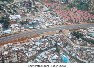 Aerial view of Nairobi, Kenya, showing modern apartment blocks alongside a sprawling township of tin roofs and squalor