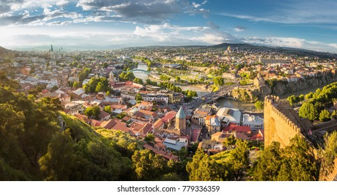 Aerial view from the Narikala fortress on the Tbilisi city, the capital of Georgia, full of small tiled roof houses, green trees, bridges over the Kura river in a sunny day