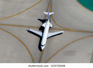 Aerial view of narrow body regional jet moving over one of the options of line at an international airport. Yellow lines going in multiple directions. Sense of options to choose from.