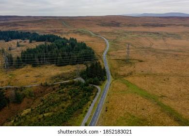 Aerial view of a narrow, winding road across rural moorland in South Wales, UK