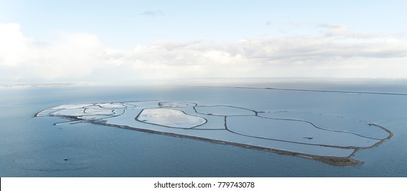 Aerial view of a nature reserve area in Lake Markermeer, Holland: The Marker Wadden, along the dike Lelystad Enkhuizen. It is a beautiful winter day. On the clear horizon Flevoland coverd with snow.