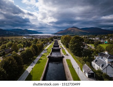 aerial view of neptune's staircase in fort william shot by drone showing a flight of locks reaching from loch linnhe to the caledonian canal during autumn with green fields and cloudy skies