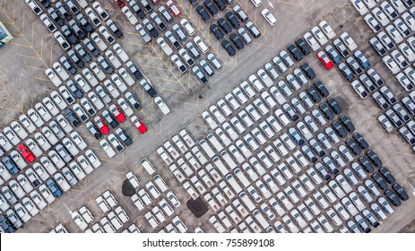 Aerial view new cars lined up in the port for import and export, car distribution centre, new cars parked in rows on a lot ready for sale.