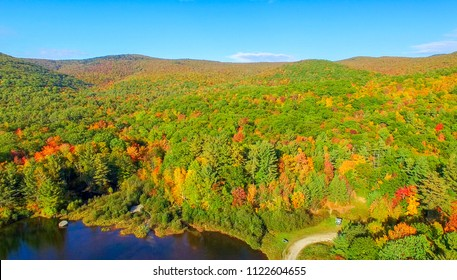Aerial view of New England foliage and lake on a sunny day.