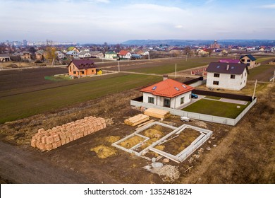 Aerial view of new house roof with attic windows and building site, foundation of future house, stacks of bricks and building timber logs for construction.