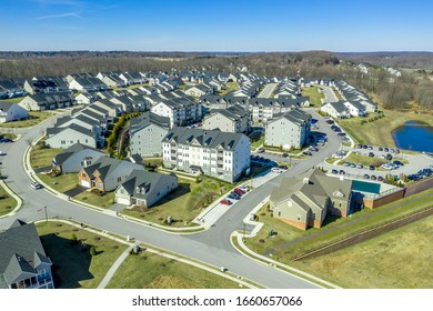 Aerial view of new middle class residential community with multifamily unit apartments, condos, duplexes, town homes and single family homes neighborhood West Waverly Maryland USA