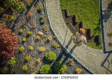 Aerial View of New Residential Garden Developing by Caucasian Landscaping Worker. Planting Flowers, Decorative Trees and Natural Grass Installation