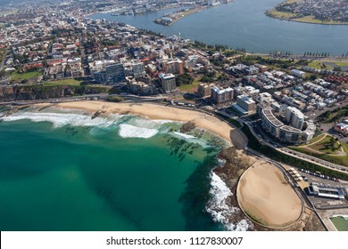 An aerial view of Newcastle beach and CBD showing residential and commercial areas and the Hunter river - Newcastle Port in the background.