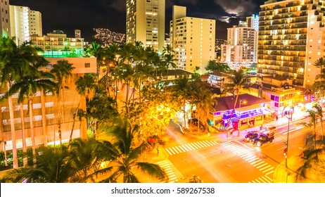 Aerial view night traffic of Waikiki city in Oahu, Hawaii, United States. Moving people and car glowing trails in the street. City night lights of shops and nightlife concept