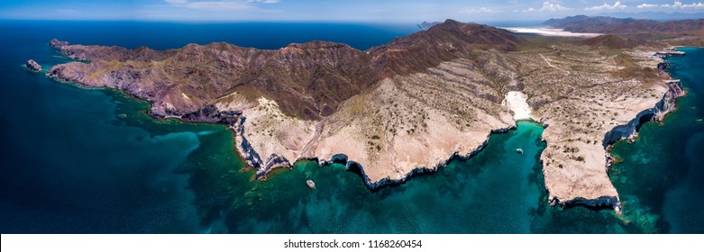 Aerial view of the northern end of Isla Carmen located near Loreto, BCS Mexico. A yacht anchors in a small cove with clear blue water.