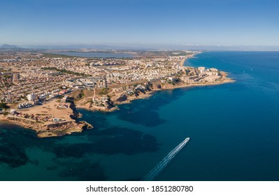 Aerial view of the northern part of the port city of Torreviejas on a sunny autumn afternoon. You can see the coastline and in the background the salt lagoon of La Mata.