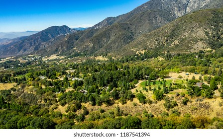 Aerial view of Oak Glen nestled between the Little San Bernardino Mountains and the San Bernardino Mountains with several apple orchards during the start of Fall just before the changing of the colors