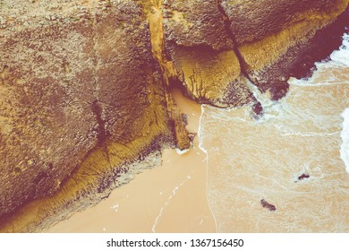 Aerial view to ocean waves. Yellow sand beach. Blue water background. Photo made from above by drone.