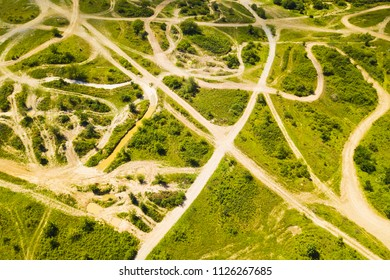 Aerial view of off-road racing track. Dusty ways in outdoor motorsport park from drone view. Background concept.