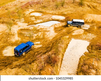 Aerial view of off-road vehicles in muddy terrain. Outdoor motor sport from drone view.