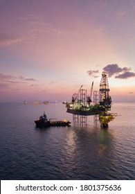 Aerial view offshore jack up rig at the offshore location during sunset with supply vessels and CPP