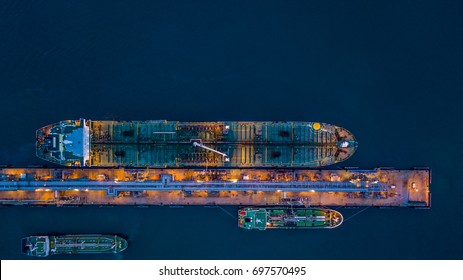 Aerial view oil tanker ship at the port in operation at night, import export business logistic and transportation.