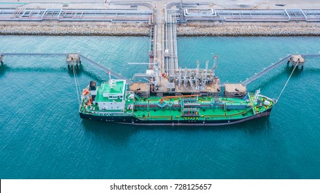Aerial view of oil tanker ship loading in port, Oil tanker ship under cargo operations on typical shore station with clearly visible mechanical loading arms and pipeline infrastructure.