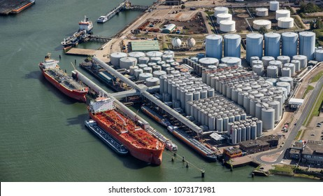 Aerial view of oil tankers moored at an oil storage silo terminal port.