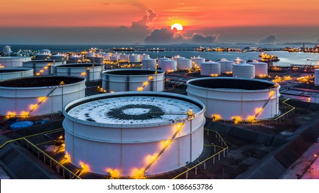 Aerial view oil terminal is industrial facility for storage of oil and petrochemical products ready for transport to further storage facilities at sunset.