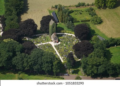 Aerial view of a old church tower covered with green ivy in Hoogzand Oostermeer, Friesland, Holland. It stands on a circle shaped cemetery surrounded by large trees.