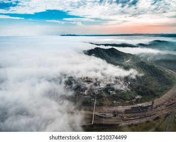 Aerial view of an old city being covered by fog in the sunset