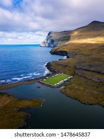 Aerial view of an old football field with scenic cliffs in the background located on the coast near the village of Eidi in Faroe Islands, Denmark. This football stadium is now used as a campsite.