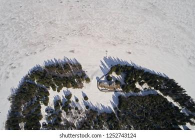 Aerial view of the old orthodox church in the forest in winter. Photo of northern wooden architecture from the drone
