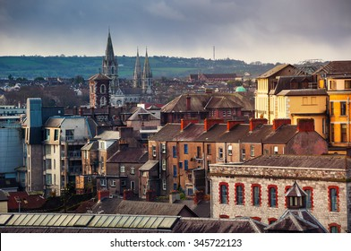 Aerial view of old part of Cork, Ireland with church and mountains at the background. Cloudy sky