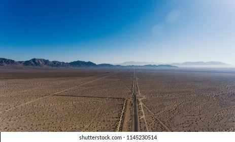 Aerial view of old pavement roadside meeting with horizon in desert lands, bird's eye view of American famous landmark Historic Route 66 crossing wild environment under dry climate sky