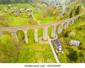 Aerial view of old railway stone viaduct. Tourist attraction in Krystofovo Udoli (Christofsgrund), Novina, Czech republic. Famous historical viaduct in Liberecky kraj, European union. - Shutterstock ID 641342449