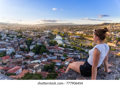 Aerial view of old Tbilisi. Georgia - happy tourist with her arms folded