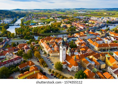 Aerial view of Old Town of Czech city of Pisek on Otava river overlooking white belfry of Church of Nativity of Blessed Virgin Mary on fall day - Shutterstock ID 1574355112